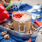 Red Pepper Walnut Dip in a mason jar, garnished with red pepper