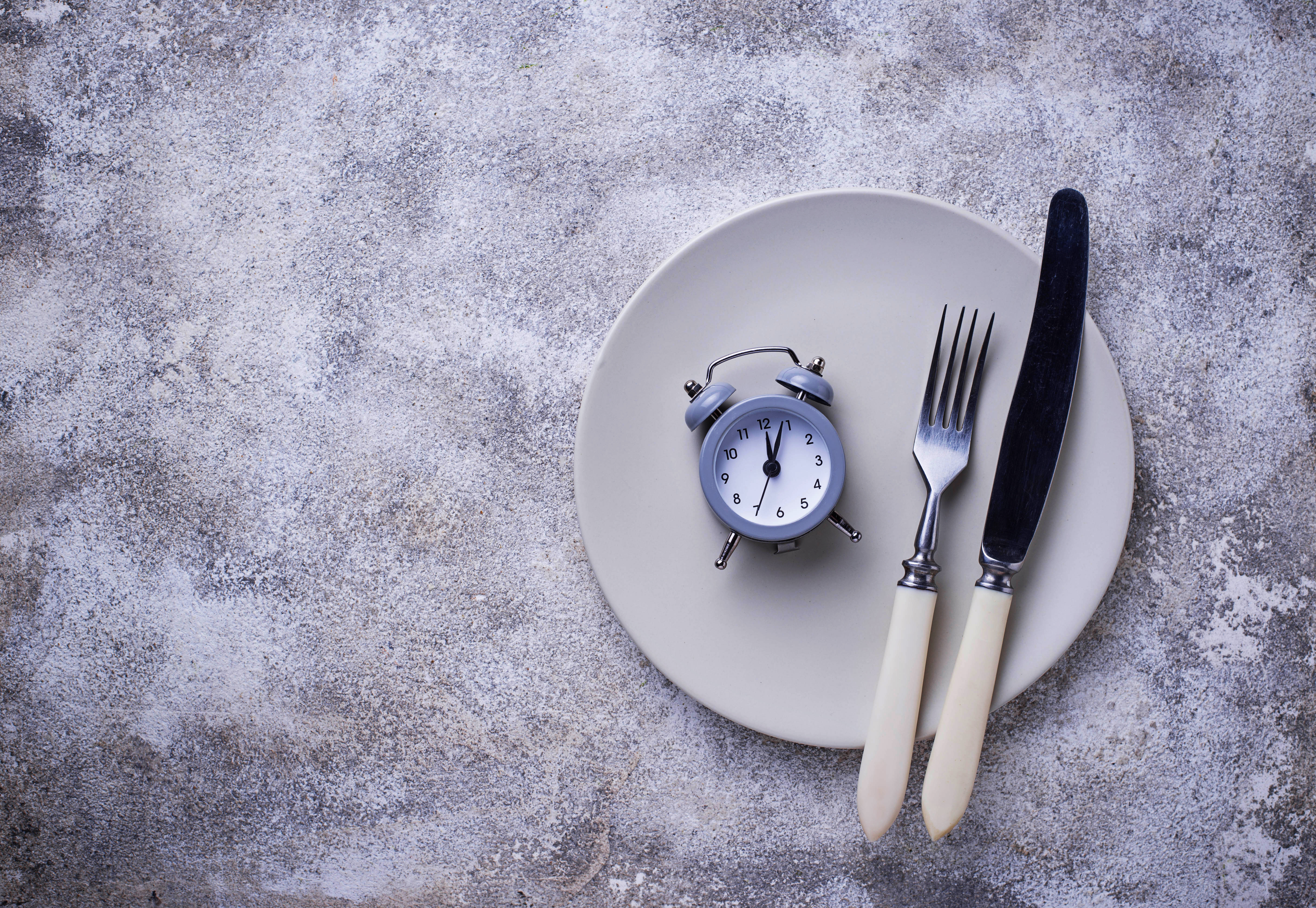 is fasting healthy?a picture of a plate with cutlery and a clock. Representing the idea of fasting and not consuming food during a certain time