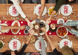 aerial photo of seven people enjoying a healthy holiday meal with a toast
