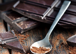 healthy dark chocolate bar on wooden table with silver spoon