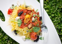 spaghetti squash noodles on white plate topped with puttanesca sauce