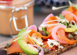 smoked salmon on flax seed crackers, garnished with avocado and capers