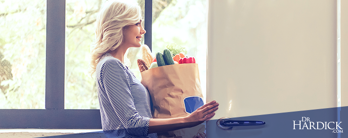 woman carrying organic groceries after spring cleaning her fridge and pantry