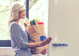girl opening fridge with groceries