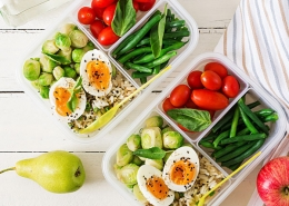 meal prep for back to school with eggs, vegetables, and a pear on a white wooden table