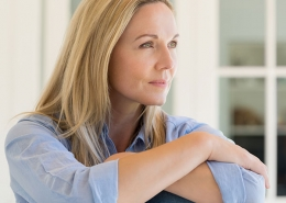 blonde woman sitting with arms folded
